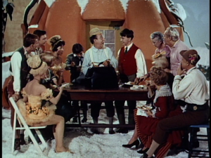 Ed Wynn (C) begins to entertain the various cast and crew members with props