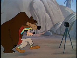 Goofy attempts to prop up the sleeping bear in the bear pit of the zoo for a photo op