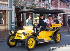 Take a ride in the yellow automobile. Or more appropriately, the Yellow Horseless Carriage. This vehicle, designed by Disney Legend Bob Gurr, first appeared on Main Street U.S.A. at Disneyland on December 6, 1956, and was the second of two Horseless Carriages to ride up and down the street carrying park guests. The first was the Red Horseless Carriage, which appeared May 12, 1956. The motorized Fire Engine appeared August 16, 1958. Prior to its appearance, there was a horse-drawn fire wagon that would carry park guests that debuted on the park's opening day, July 17, 1955. The fire wagon is now on permanent display inside the Disneyland Fire Department fire station.